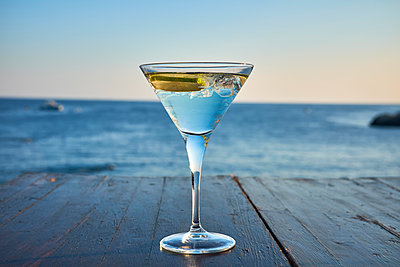 Glass of ice-cooled Martini with lime slice in front of the sea - p300m1505552 by Dirk Kittelberger