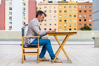 Businessman sitting on roof terrace working on laptop - p300m2012240 by VITTA GALLERY