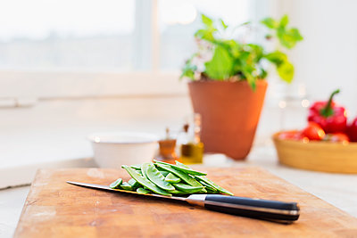 green peas and knife on chopping board - p312m1180354 by Jakob Fridholm