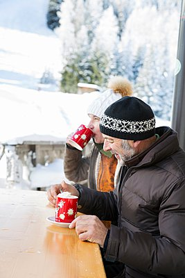 Side view of senior couple sitting at table drinking hot chocolate, Sattelbergalm, Tyrol, Austria - p429m1080079f by Manuela