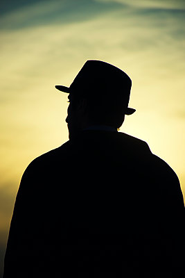 Silhouette of a man wearing a hat looking away at sunset  - p794m1508349 by Mohamad Itani