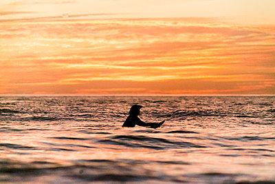 Woman on surfboard paddling in ocean  - p919m2108332 by Beowulf Sheehan