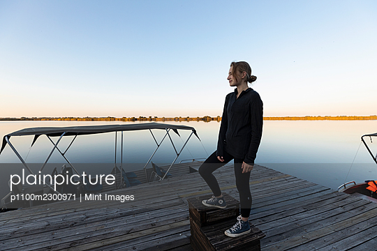 Teenage girl, silhouette at dusk, on a jetty on the Okavango Delta - p1100m2300971 by Mint Images