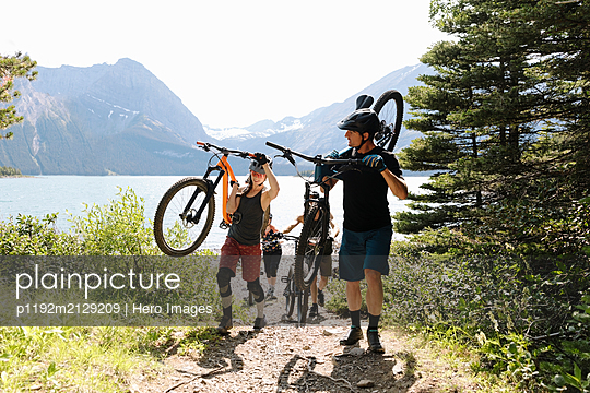 Friends mountain biking on trail in sunny woods at lakeside - p1192m2129209 by Hero Images