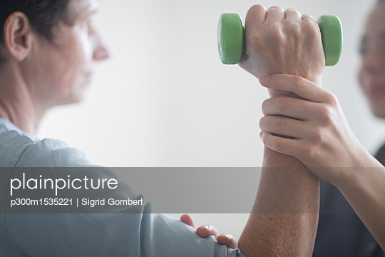 Physiotherapist and patient, training with dumbbell - p300m1535221 by Sigrid Gombert