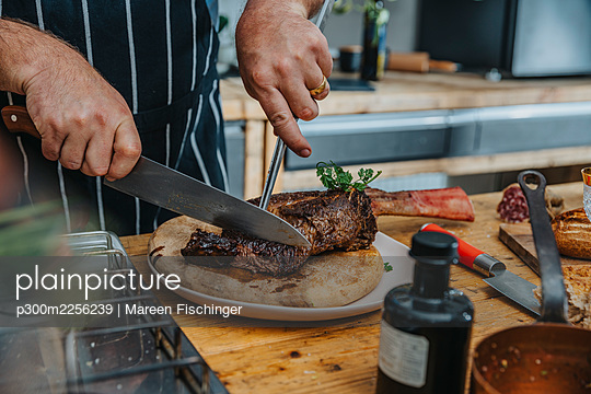 Expertise cutting cooked tomahawk steak in plate while standing in kitchen - p300m2256239 by Mareen Fischinger