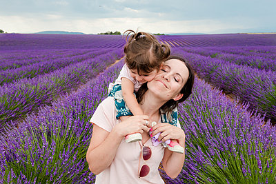 Mother and daughter walking among lavender fields in the summer - p1166m2136648 by Cavan Images
