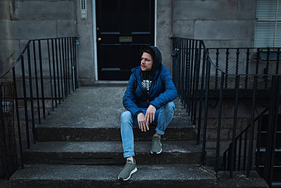 Young man in front of townhouse - p1477m2038910 by rainandsalt