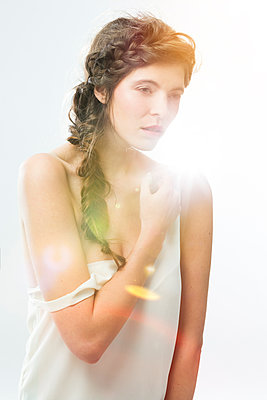 Portrait of woman with braid in front of white background at backlight - p300m1068939f by Sarah Kastner