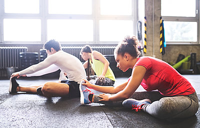 Three young people stretching in gym - p300m1470162 by HalfPoint