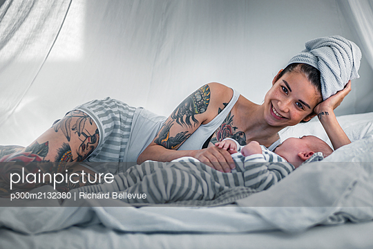 Portrait of smiling tattooed young woman with her baby in canopy bed - p300m2132380 by Richárd Bellevue