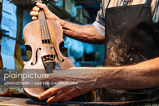 Violin maker examining violin for repairing at workshop - p300m2214081 by Jose Luis CARRASCOSA