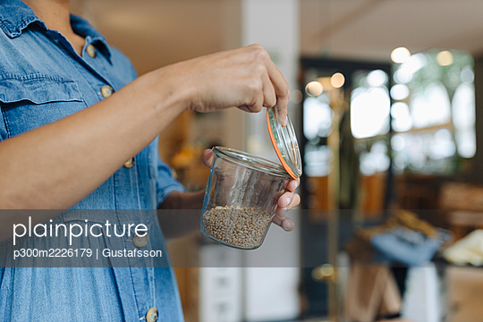 Midsection of female owner opening food jar while standing in cafe - p300m2226179 by Gustafsson