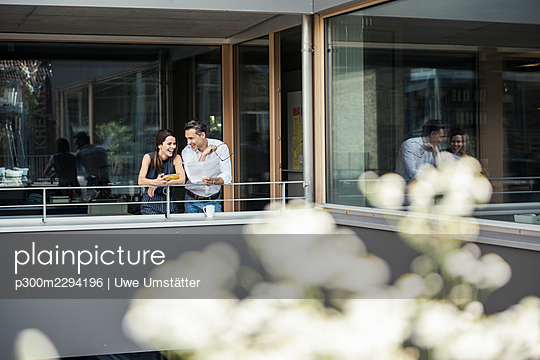 Smiling businessman discussing with colleague at office balcony - p300m2294196 by Uwe Umstätter