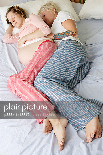 Caucasian pregnant lesbian couple laying on bed - p555m1418817 by Janet Kimber