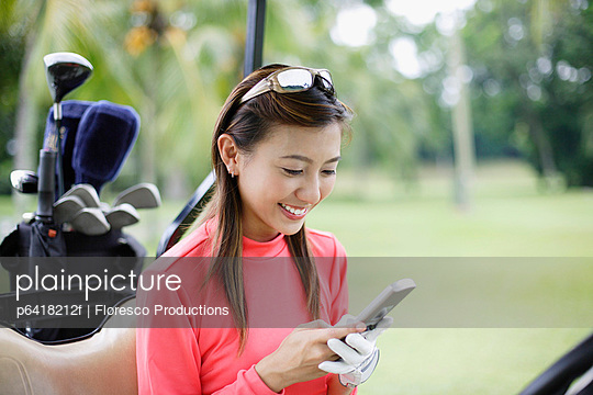 Woman in a golf cart looking at her mobile phone