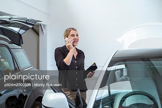 UK, Woman talking on smart phone next to her car in parking garage - p924m2300839 by Monty Rakusen