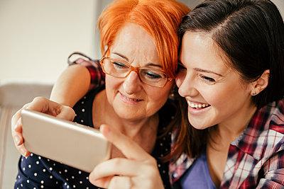Happy adult daughter with mother taking a selfie - p300m1356531 by Zeljko Dangubic