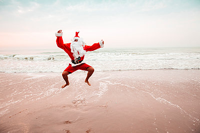 Thailand, man dressed up as Santa Claus jumping in the air on the beach - p300m2083501 by Epiximages