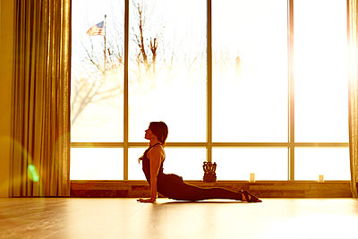 A female practicing yoga in a yoga studio - p343m1173316 by Josh Campbell