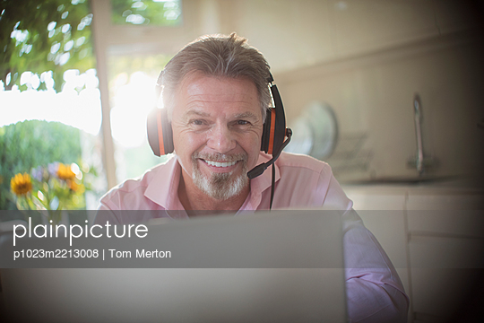 Portrait smiling senior man with headphones working at laptop - p1023m2213008 by Tom Merton