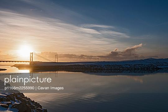 arctic pale winter sun over bridge on JÌŠkulsÌÁrlÌ_n - p1166m2255990 by Cavan Images