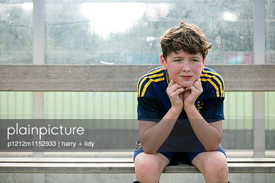 Junge auf der Bank auf dem Sportplatz - p1212m1152933 von harry + lidy