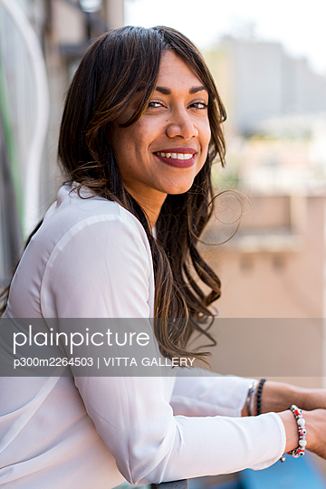 Beautiful smiling businesswoman in balcony at office - p300m2264503 by VITTA GALLERY