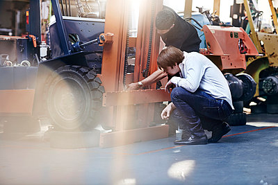 Mechanic and customer examining forklift in auto repair shop - p1023m1058925f by Trevor Adeline