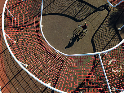 Man cycling in sports field, aerial view - p300m2202775 by Konstantin Trubavin
