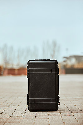 Black suitcase on footpath against clear sky - p300m2250071 by Aitor Carrera Porté