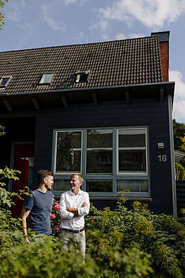 Father and son talking to each other while standing in backyard - p300m2276916 by Gustafsson