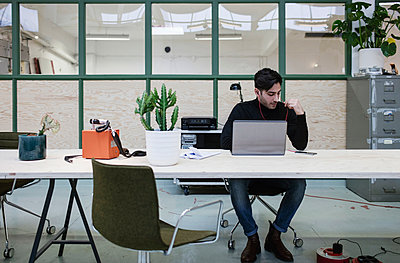 Male blogger sitting with laptop at desk in office - p426m1407179 by Maskot
