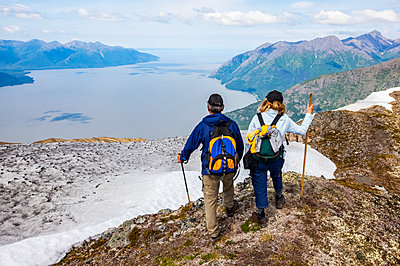 Hikers in the Chugach Mountains South of Anchorage, South-central Alaska. Summer. Couple is overlooking Turnagain Arm and the Seward Highway; Alaska, United States of America - p442m2154203 by Doug Lindstrand