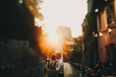 Caucasian couple hugging in city street at sunset - p555m1219639 by Sophie Filippova