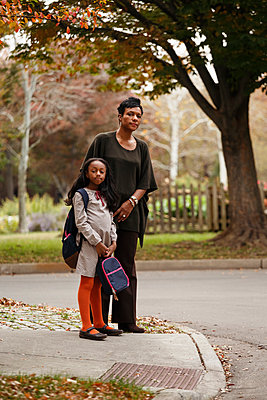 African American woman and daughter waiting for school bus - p555m1413277 by Roberto Westbrook