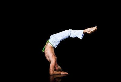 Man practising capoeira - p924m742140 by Dean Northcott