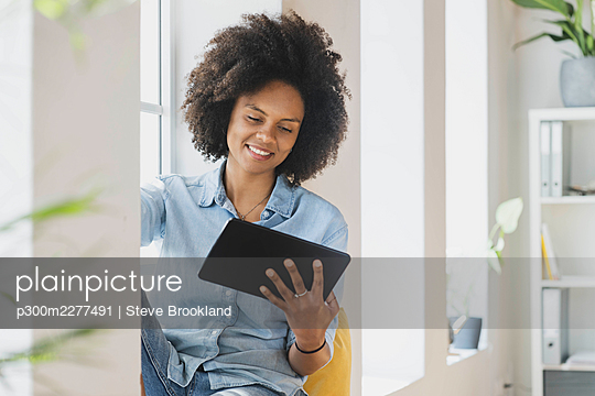Smiling woman using digital tablet while sitting at window - p300m2277491 by Steve Brookland