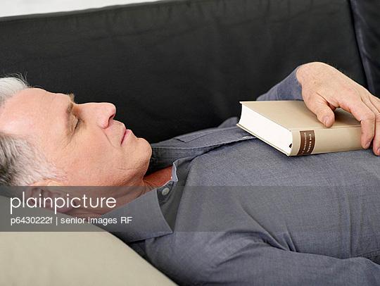 Aelterer Mann schlaeft auf dem Sofa  - p6430222f von senior images RF