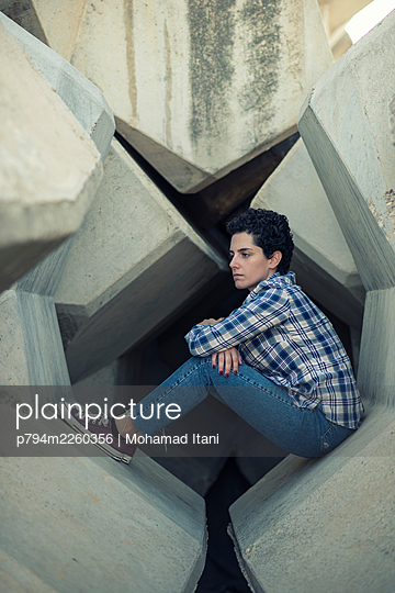 Sad young woman sitting on concrete blocks looking away  - p794m2260356 by Mohamad Itani