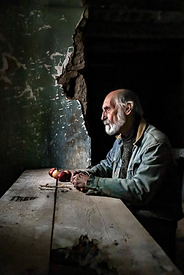 Senior man in rustic room at Table with Apples - p1019m2135192 by Stephen Carroll