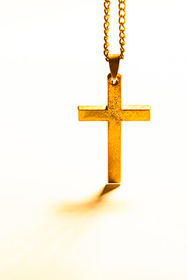 An old metal cross or crucifix hanging from a metal chain, a religious icon or symbol often used by the christian faith. - p1057m1572925 by Stephen Shepherd