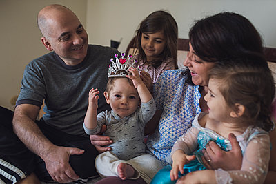 Entire family in parent's bed laughing at 1 yr old baby wearing tiara - p1166m2213027 by Cavan Images