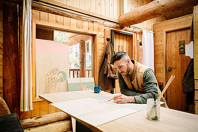Male artist drawing at cabin table - p1192m2093899 by Hero Images