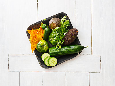 Wooden bowl of avocados, green tomatoes, Jalapeno peppers, cucumber and tortilla chips - p300m1568170 von Kai Schwabe