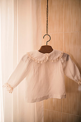 White crop top hanging from coathanger at workshop - p300m2293495 by LUPE RODRIGUEZ