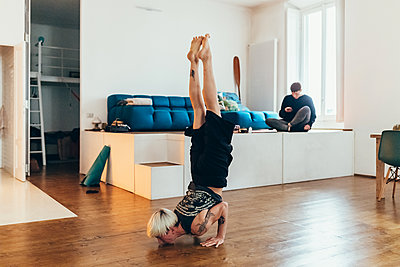 Woman practising yoga at home, friend in background - p429m2032678 by Eugenio Marongiu