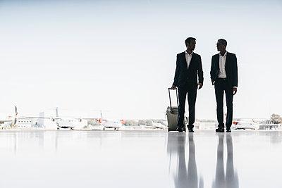 Two businessmen on airfield - p586m1208575 by Kniel Synnatzschke