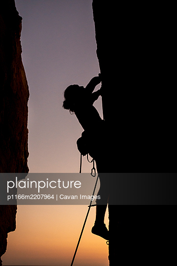 Beautiful view to silhouette of man climbing during sunset - p1166m2207964 by Cavan Images