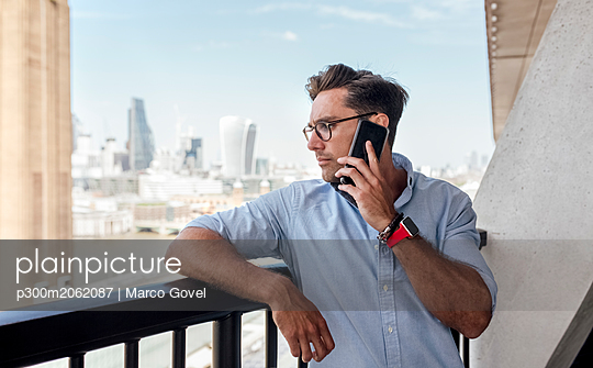 UK, London, man on the phone on a roof terrace - p300m2062087 by Marco Govel